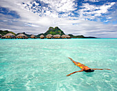 French Polynesia, Tahiti, Bora Bora, Woman floating in water near resort.