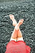 Girls legs, feet in air on black rocks.