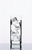 Tall clear glass filled with water and ice cubes.