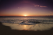 Hawaii, Oahu, North Shore, water lapping onto shore of a beautiful sandy beach at sunset.