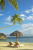 French Polynesia, Tahiti, Bora Bora, Lounge chairs and thatch umbrella on beach with tranquil ocean and bungalows