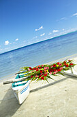 French Polynesia, Huahine, Outrigger canoe on the shore of a tropical beach, decorated with beautiful flowers for a wedding