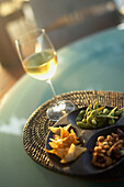 Hawaii, Big Island, Four Seasons Hualalai, white wine in glass and pupus on table.
