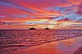 Hawaii, Oahu, Lanikai, A colorful pink sunrise over the Mokulua islands.