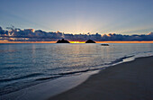 Hawaii, Oahu, Lanikai, sunrise with the Mokulua islands and outrigger canoe in the distance.