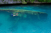 Micronesia, Palua, couple with scuba gear explore a shallow wreck.