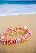 Hawaii, Turquoise ocean waters, foaming shore water, pink plumeria lei, ALOHA written in sand