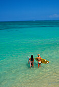 Two females walk into ocean holding surfboards, view from behind, beautiful turquoise ocean out to horizon, blue sky