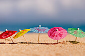 Close-up of cocktail umbrella's in the sand