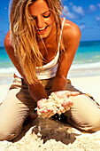 Teenage girl kneeling on beach in white tank/khakis looking at/playing with sand.