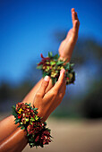 Close-up of hula hands with flower bracelets