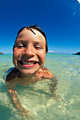Hawaii, Oahu, Kailua, Extreme close-up of young boy laying in shallow ocean, smiling, cloudless blue sky