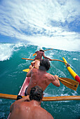 Close-up back view local men riding wave in outrigger canoe D1440