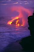Hawaii, Big Island, Kilauea Volcano, lava meets ocean action, glowing in pink steamy skies