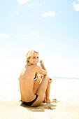 Hawaii, Kauai, Kealia, Beautiful blonde model poses on beach.