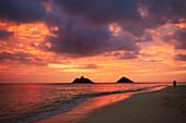 Hawaii, Oahu, Kailua, Lanikai, Vibrant sunset with a couple embracing on beach.