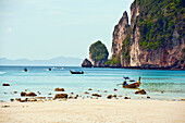 Thailand, Koh Phi Phi, Longtail boats along the shoreline, Mountains in distance.