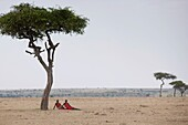 'Two Men Sitting On The Plain; Kenya, Africa'