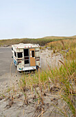 A motorhome or camper, an RV parked on a beach by sand dunes. Back door open. Fishing gear in the back of the vehicle., Cape Disappointment State Park, Washington, USA