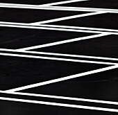 A car park, indoors parking lot, with a freshly resurfaced, black top surface, with newly painted white lines marking the parking bays. Pattern., Los Angeles, California, USA. Parking Lot