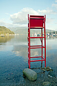 A tall empty wooden lifeguard chair painted red,  overlooking the clear calm waters of Deep Cove. , Indian Arm in Deep Cove, North Vancouver, BC, Canada