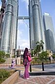 Malaysia, Kuala Lumpur, woman phoning in front of Petronas Towers