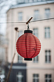 Red paper lampion hung up, Berlin, Germany