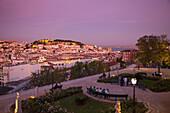 Miradouro Sao Pedro de Alcantara in Chiado district with views across Baixa district and Castelo de San Jorge, St. George's Castle, at dusk, Lisbon, Lisboa, Portugal