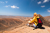 Woman sitting on the top of a mountain, view point, Pajara, Betancuria, Fuerteventura, Canary Islands, Spain, Europe