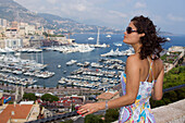 Young woman and view towards Port, Hercule, Palais, Monaco, Monte Carlo, Cote d Azur, France, Europe