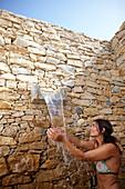 Frau in Außendusche an Natursteinmauer, Hotel Areias do Seixo, Povoa de Penafirme, A-dos-Cunhados, Costa de Prata, Portugal