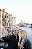 Couple taking pictures of themselvs on bridge Ponte dell Accademia at the Grand Canal, Venice, Veneto, Italy