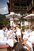 Children sitting on the terrace of Hotel Haus Wirt in bathrobes after swimming, Bad Gastein, St. Johann im Pongau, Salzburg, Austria