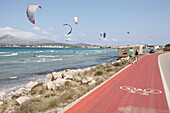 Tourists walking along a bike lane next to the coastal road, kite surfers near Club Pollentia, Badia de Pollenca near Alcudia, Mallorca, Balearic Islands, Spain