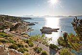 Coastal road leads to S'Illot chapel, view over Playa S'Illot beach, Alcudia peninsula, bay of Pollenca, Mallorca, Balearic Islands, Spain