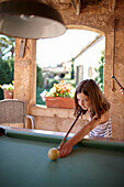 Girl playing billiards at a roofed terrace, Algaida, Mallorca, Balearic Islands, Spain