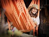 Woman in sunhat relaxing in hammock