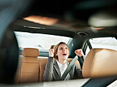 Businesswoman cheering in car