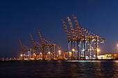 Cranes in shipyard lit up at night