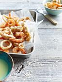 Pan of fried seafood with sauce. Salt And Pepper Seafood _ Prawns, Calamari, Fish Pieces, Lemon Aioli