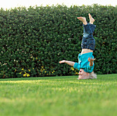 Boy balancing on his head in backyard