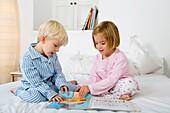 Siblings reading a book in their pyjamas