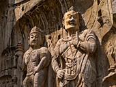 Statue of Vaisravana and warrior  North wall of Fengxiansi Cave  The grottoes were started around the year 493 when Emperor Xiaowen of the Northern Wei Dynasty 386-534 moved the capital to Luoyang and were continuously built during the 400 years until the