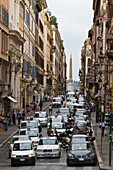A narrow street with cars in central Rome, Italy