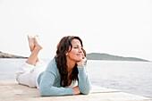 Pretty brunette woman lying on a seaside Pier