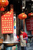 China, Sichuan, Luding, Street scene, Woman cooking food
