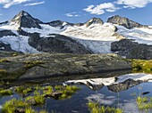 Valley head of valley Obersulzbachtal in the NP Hohe Tauern  The Peaks of Mt  Grosser Geiger and Mt  Maurerkeeskopf with a perfect reflection in a glacial pond  The National Park Hohe Tauern is protecting a high mountain environment with its characteristi