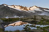 Valley head of valley Obersulzbachtal in the NP Hohe Tauern  The peaks of the Schliefer towers and Mt  Schlieferspitz towering above the glacier Sonntagskees with a perfect reflection in a glacial pond  The National Park Hohe Tauern is protecting a high m
