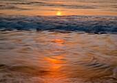 Waves breaking near shore at sunrise