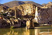 Remains of medieval Artukid Old Tigris Bridge â Built in 1116 by Artukid Fahrettin Karaaslan, the biggest in Anatolia at the time, with the old town Hasankeyf and its ruins on the cliffs abover the river Tigris  The minaret is of the El Rizk Mosque built.
